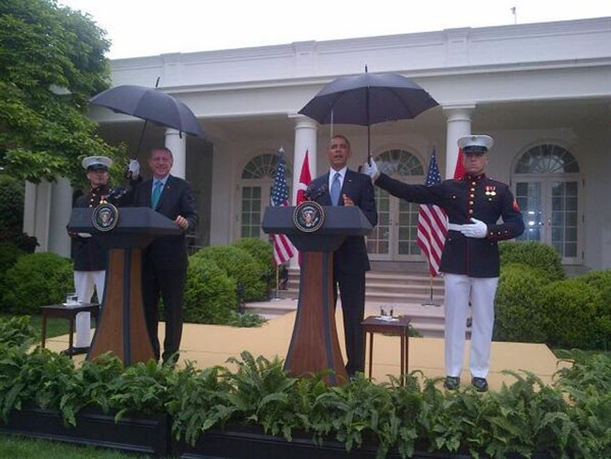 U.S. Marines use umbrellas to keep President Obama and the Turkish prime minister dry during a news conference in the Rose Garden. (Twitter/Major Garrett)