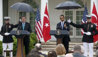 Marines hold umbrellas as President Barack Obama and Turkish Prime Minister Recep Tayyip Erdogan participate in a joint news conference in the Rose Garden of the White House in Washington, Thursday, May 16, 2013. (AP Photo/Charles Dharapak)