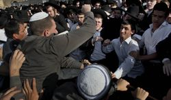 """** FILE ** Ultra-orthodox Jewish men scuffle with Israeli security forcers during a prayer organized by the """"Women of the Wall"""" organization, not pictured, at the Western Wall, the holiest site where Jews can pray in Jerusalem's old city, Friday, May 10, 2013. (AP Photo/Bernat Armangue)"""