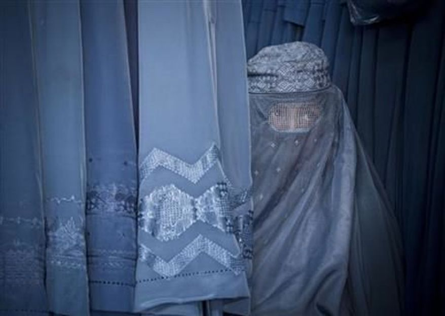 ** FILE ** Afghan woman peers through the the eye slit of her burqa as she waits to try on a new burqa in shop in the old town of Kabul, Afghanistan, April 11, 2013. Religious lawmakers in Afghanistan blocked a law on Saturday, May 18, 2013 that aims to protect women's freedoms. (AP Photo/Anja Niedringhaus, File)