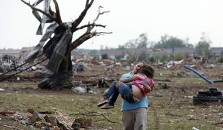A woman carries a child through a field near the collapsed Plaza Towers Elementary School in Moore, Okla., on May 20, 2013. A tornado as much as half a mile wide with winds up to 200 mph roared through the Oklahoma City suburbs, flattening entire neighborhoods, setting buildings on fire and landing a direct blow on an elementary school. (Associated Press)