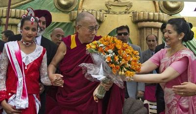 ** FILE ** School children welcome Tibetan spiritual leader the Dalai Lama, center, with a bouquet of flowers at the Dalhousie Public School in Dalhousie, about 130 kilometers (80 miles) north-west of Dharmsala, India, Sunday, April 28, 2013. The Dalai Lama arrived in Dalhousie Saturday on a two-day visit. (AP Photo/ Ashwini Bhatia)