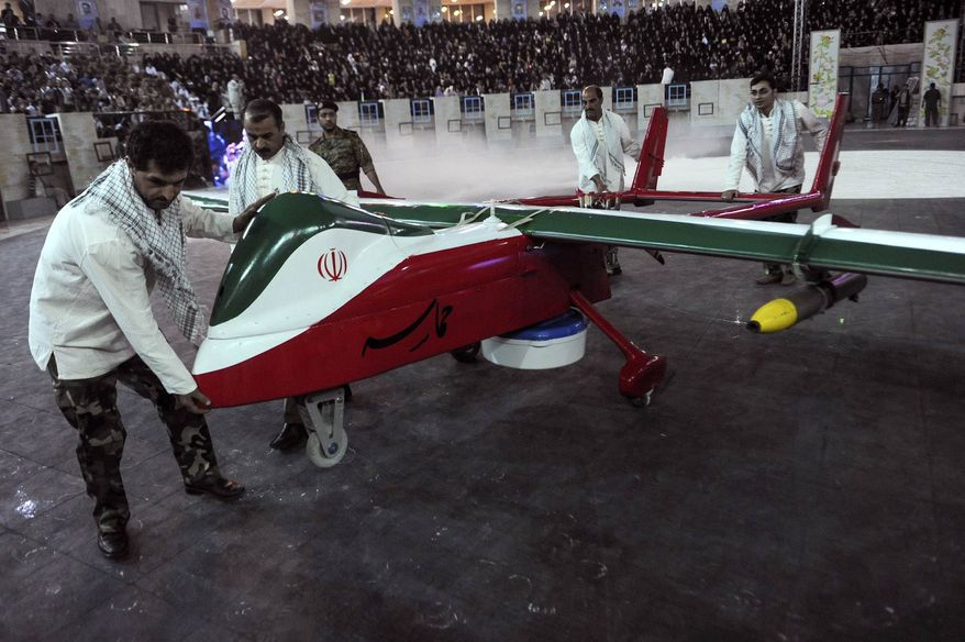 **FILE** In this photo released by the Iranian Students News Agency, men move the Epic drone, painted with the Iranian flag colors, during a ceremony in Tehran on May 9, 2013. Iran's defense minister says Iran has built a new, radar-evading drone that can do surveillance and fire on enemy targets. (Associated Press/ISNA)