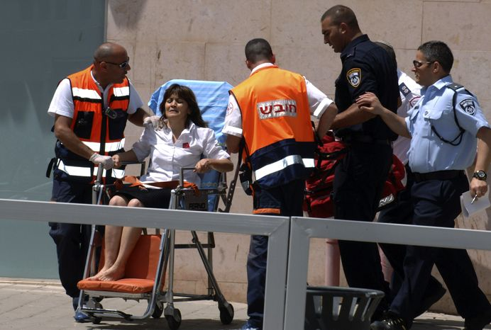 An woman is taken out of a bank in Beersheba, Israel, on Monday, May 20, 2013, after a gunman stormed into the bank in the southern Israeli city in what authorities called either a robbery gone wrong or a revenge killing. (AP Photo/Dudu Greenspan)