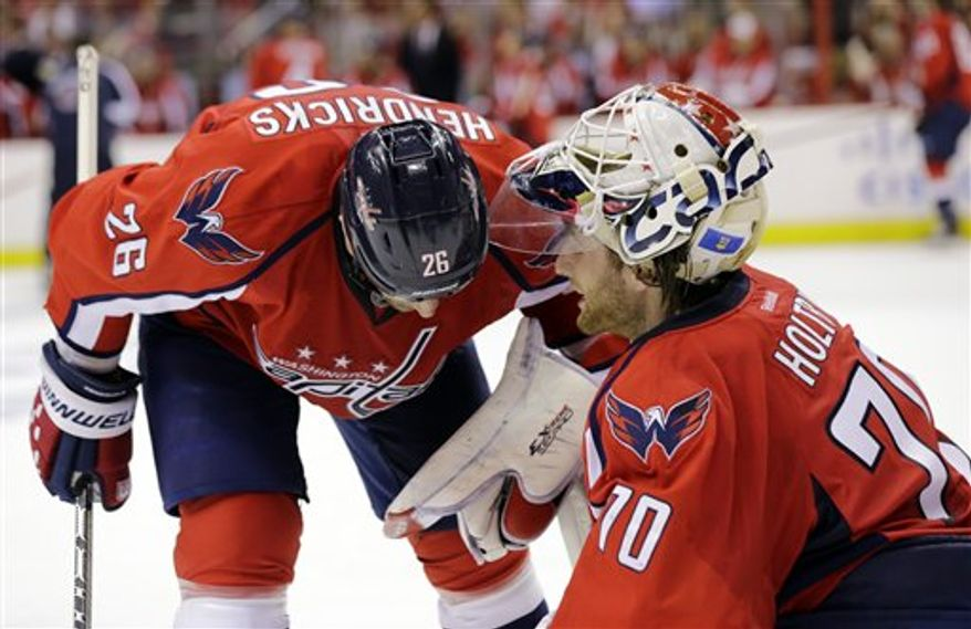 Washington Capitals center Matt Hendricks (26) talks with Washington Capitals goalie Braden Holtby (70) in the third period of Game 5 first-round NHL Stanley Cup playoff hockey series against the New York Rangers, Friday, May 10, 2013 in Washington. (AP Photo/Alex Brandon)