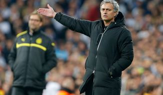 **FILE** Real Madrid's coach Jose Mourinho from Portugal gestures, with Dortmund's coach Juergen Klopp in the background, left, during the Champions League semifinal second leg soccer match between Real Madrid and Borussia Dortmund at the Santiago Bernabeu stadium in Madrid, Spain, Tuesday April 30, 2013. (AP Photo/Paul White)
