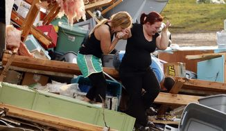 Alli Christian, left, helps Jessica Wilkinson as she looks for her dog Bella after Wilkinson returned to find her home near 156th street and Franklin Road destroyed by a tornado on Sunday, May 19, 2013, in Norman, Okla. (AP Photo/The Oklahoman, Steve Sisney)