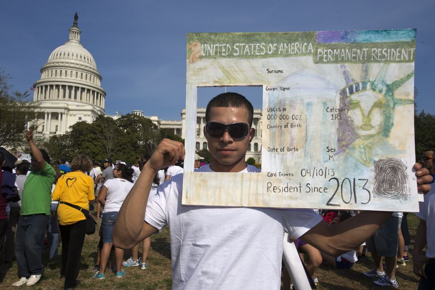 "**FILE** Roberto Morales, 25, holds a sign representing a permanent resident card while attending the ""Rally for Citizenship"" on Capitol Hill on April 10, 2013, in support of immigration reform. (Associated Press)"