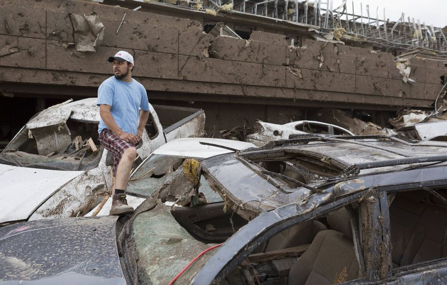 Antonio Flores of Moore, Okla., searches for his car after a tornado damaged the Moore Medical Center and the vehicles in the parking lot in Moore, Okla. on Monday, May 20, 2013. (AP Photo/Alonzo Adams)
