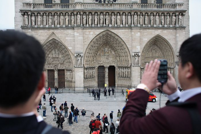 Tourists take pictures as police officers stand guard in front of Notre Dame Cathedral in Paris on Tuesday, May 21, 2013. The church was evacuated after a man committed suicide in the 850-year-old monument and tourist attraction. (AP Photo/Thibault Camus)