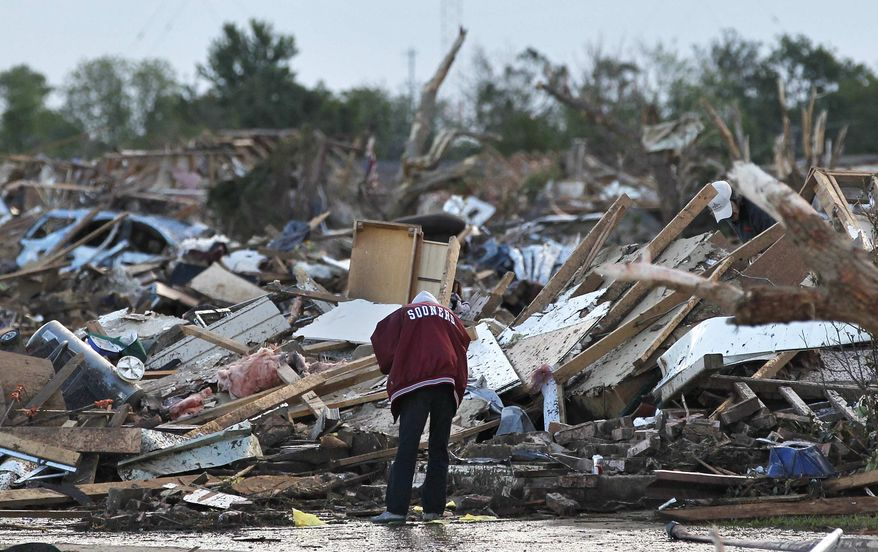 A local resident allowed looks through the rubble of a destroyed home, one day after a tornado moved through Moore, Okla., Tuesday, May 21, 2013. (AP Photo/Brennan Linsley)