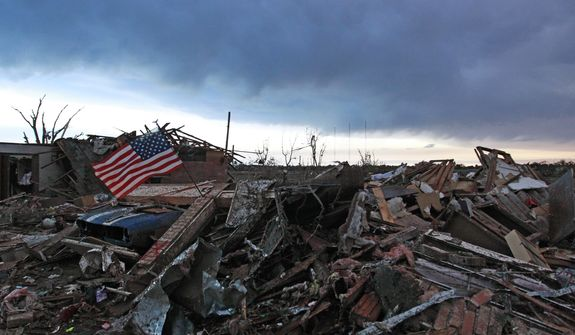 An American flag blows in the wind at sunrise atop the rubble of a destroyed home a day after a tornado moved through Moore, Okla., Tuesday, May 21, 2013. (AP Photo/Brennan Linsley)