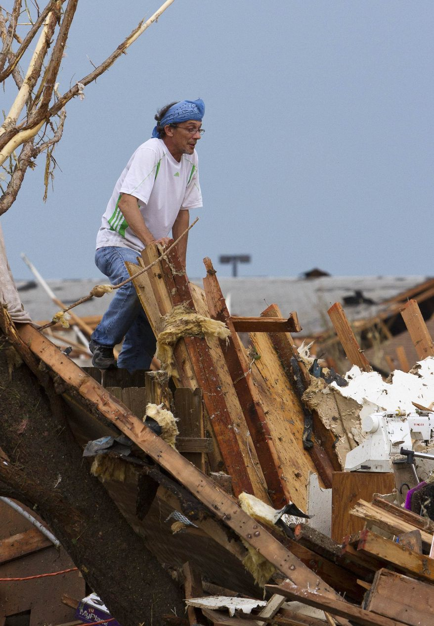 A man searches a damaged home near SW 4th Street and Telephone Road after a tornado moved through Moore, Okla., on Monday, May 20, 2013. (AP Photo/Alonzo Adams)