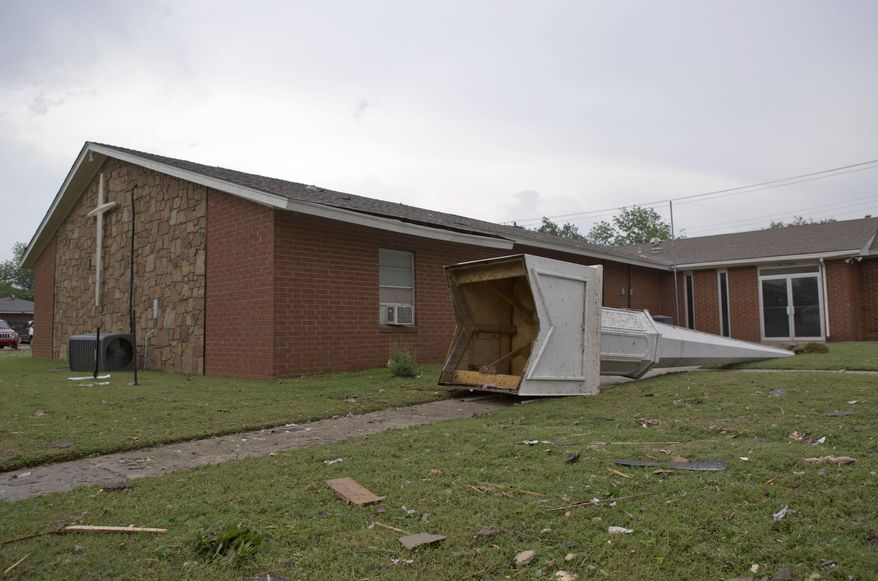 The steeple of a church at South Janeway Avenue and SW 4th Street lays across the lawn after a tornado moved through Moore, Okla., on Monday, May 20, 2013. (AP Photo/Alonzo Adams)
