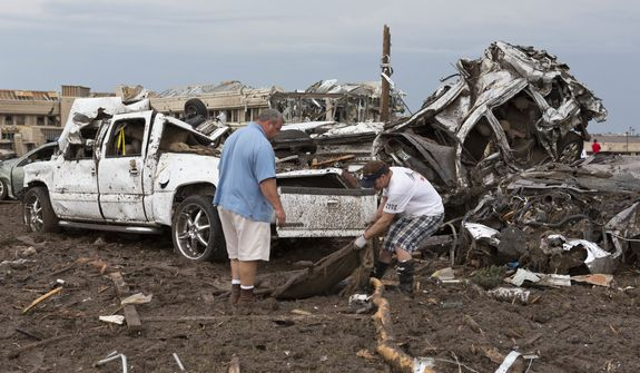 Two men go through the damage surrounding the Moore Medical Center after a tornado moves through Moore, Okla., on Monday, May 20, 2013. (AP Photo/Alonzo Adams)