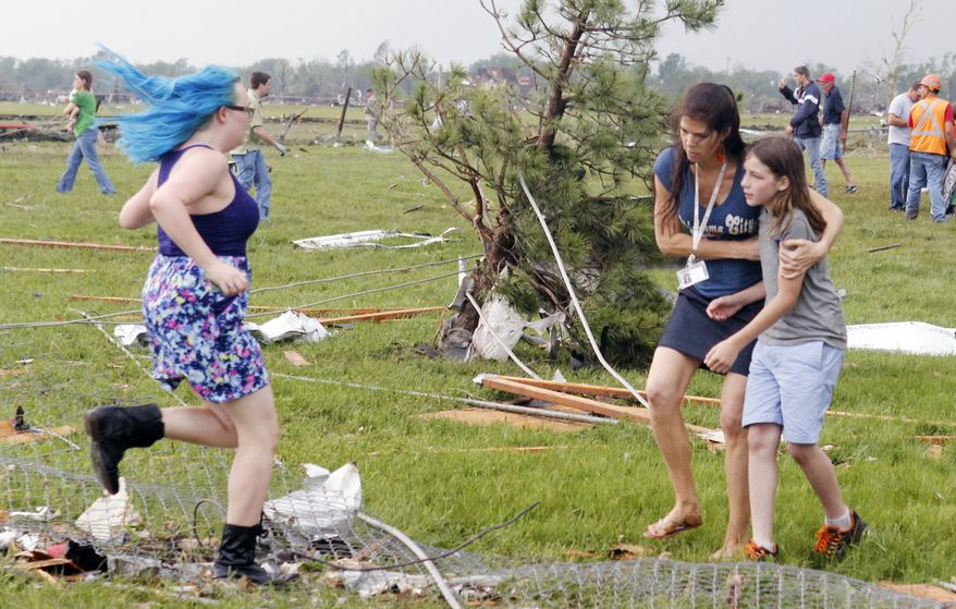 A parent rushes to embrace her child as a teacher escorts her away from Briarwood Elementary school after a tornado destroyed the school in south Oklahoma City, Okla,, Monday, May 20, 2013, near SW 149th and Hudson. (AP Photo/ The Oklahoman, Paul Hellstern)