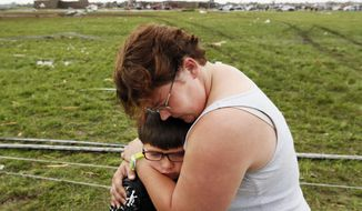 Rebekah Stuck hugs her son, Aiden, 7, after she found him in front of the destroyed Briarwood Elementary School after a tornado struck south Oklahoma City and Moore, Okla., on Monday, May 20, 2013. Aiden was inside the school when it was hit. (AP Photo/The Oklahoman, Nate Billings)