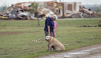 Kay Taylor stands with her dog Bailey in front of her house that was destroyed after the tornado that hit the area near 149th and Drexel on Monday, May 20, 2013, in Oklahoma City, Okla. (AP Photo/The Oklahoman, Chris Landsberger)