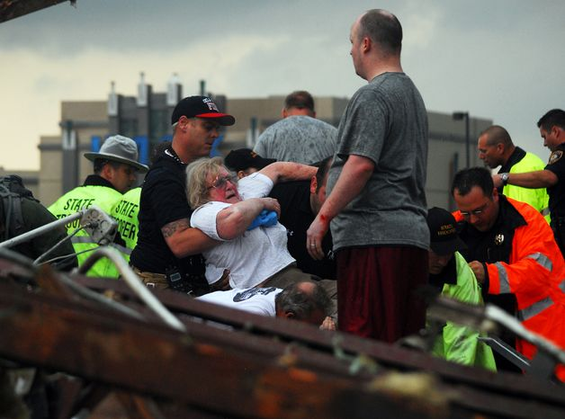 Emergency workers pull out a woman who was trapped in a building that was destroyed when a tornado ripped through Moore, Okla., on Monday, May 20, 2013. (AP Photo/The Transcript, Kyle Phillips )