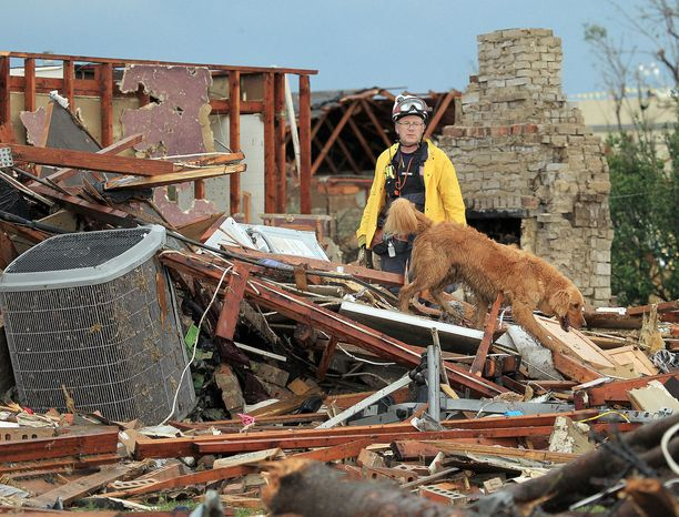 A rescue worker with his search dog looks through the remains of a home in Moore, Okla. Residents were allowed to return to their homes for the first time Wednesday, with local officials confident there are no more victims buried beneath the rubble. (Dallas Morning News via Associated Press)