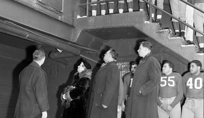 Surrounded by New York football Giants, members of the family of the late Al Blozis, former Giant and Georgetown football and shot put star killed in the war, look at memorial plaques after its unveiling at New York's Polo Grounds prior to the Giant's Philadelphia Eagles game, Dec. 2, 1945. In the center are Mr. and Mrs. Anthony Blozis, Al's parents and his brother, Joseph, right.(AP Photo/Harry Harris)
