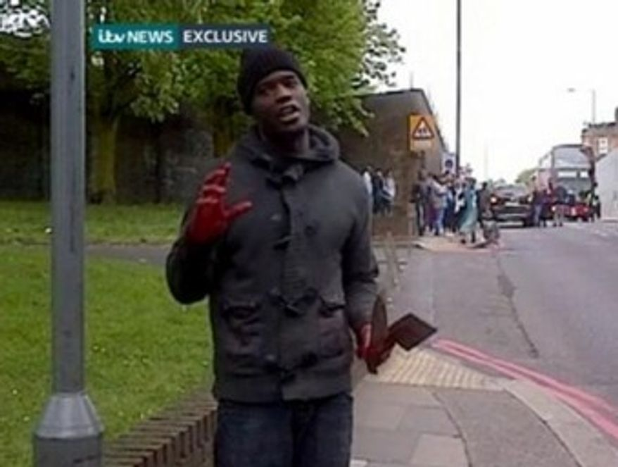 A man stands in a London street after allegedly screaming, 'Allahu Akbar,' and killing a man in broad daylight. (ITV news screenshot)
