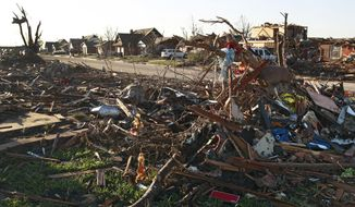The wreckage of a row of completely leveled homes sits across from a row of partially destroyed houses on Wednesday, May 22, 2013, two days after a tornado moved through Moore, Okla. (AP Photo/Brennan Linsley)