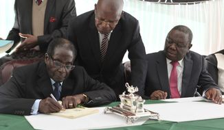 Zimbabwean President Robert Mugabe (left) signs the new Zimbabwe Constitution while Prime Minister Morgan Tsvangirai (right) looks on at State House in Harare, Zimbabwe, the capital, on Wednesday, May 22, 2013. The signing of the new constitution paves way for elections to be held later in the year. (AP Photo/Tsvangirayi Mukwazhi)
