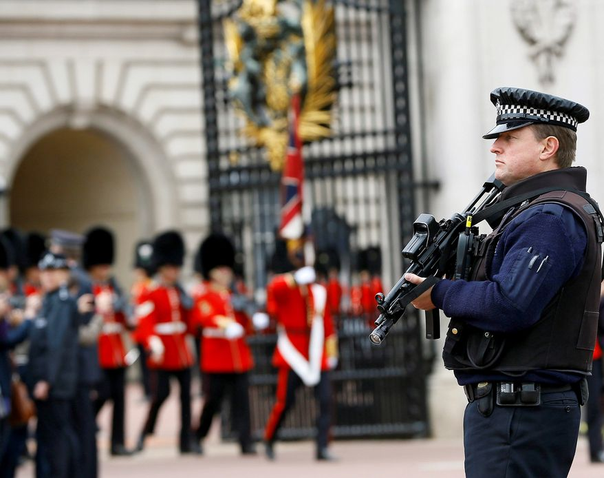 An armed police officer keeps guard as British soldiers march out of Buckingham Palace after the changing of the guard ceremony in London, Thursday, May 23, 2013. Britain was coming to terms with an apparent return of terrorism to its capital Thursday as new information emerged about the butchering of a British soldier near an army barracks in Woolwich by suspected Islamic radicals. (AP Photo/Kirsty Wigglesworth)