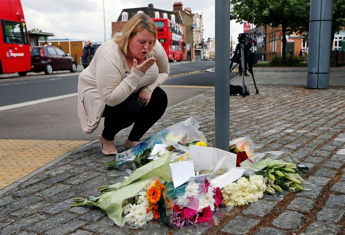 ** FILE ** A woman blows a kiss as she lays a floral tribute in memory of the victim outside the Royal Artillery Barracks near the scene of a terror attack in Woolwich in southeast London on Thursday, May 23, 2013. A member of the armed forces was attacked and killed by two men on Wednesday. (AP Photo/Sang Tan)
