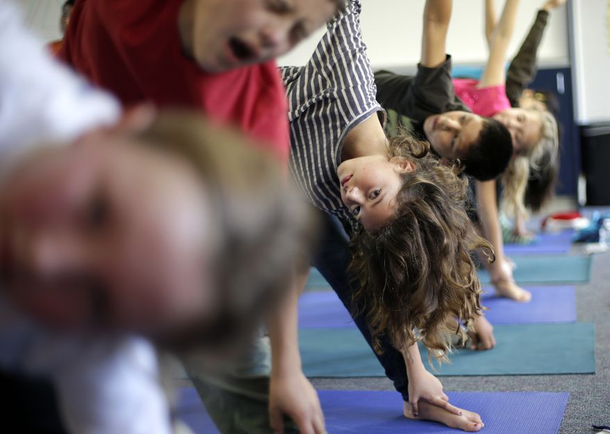 Students hold their position during a yoga class at Capri Elementary School in Encinitas, Calif., on Wednesday, Dec. 11, 2012. (AP Photo/Gregory Bull)