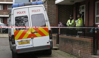 Police officers guard a flat as it is being searched at Greenwich in southeast London on May 23, 2013. A member of the armed forces was attacked and killed by two men on Wednesday at nearby Woolwich. (Associated Press)