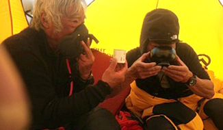 In this May 22, 2013, photo distributed by Miura Dolphins Co. Ltd., 80-year-old Japanese extreme skier Yuichiro Miura, left, uses oxygen mask and his son, Gota sips green tea as they take a rest in a tent at their South Col camp at 8,000 meters (26,247 feet) before their departure for Camp 5 during their attempt to scale the summit of Mount Everest. (AP Photo/Miura Dolphins Co. Ltd.)