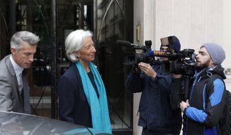 International Monetary Fund Managing Director Christine Lagarde leaves her apartment building in Paris for a French court on Thursday, May 23, 2013. Ms. Lagarde is being investigated by the special court over a controversial arbitration deal that she oversaw as French finance minister in 2008. (AP Photo/Thibault Camus)
