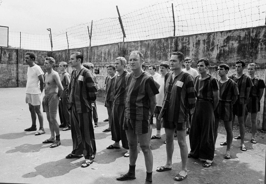 ** FILE ** In this March 29, 1973, file photo, unidentified U.S. prisoners of war stand in the courtyard of Hanoi's POW camp at Nga Tu So street waiting for an inspection of the camp by joint military and international control and supervision commissions. On Thursday, May 24, 2013, some 200 former POWs, almost all of them former pilots, will reunite for a three-day celebration at the Richard Nixon Presidential Library & Museum in Yorba LInda, Calif., that coincides with the 40th anniversary of a star-studded White House dinner hosted by President Nixon to honor their sacrifice. (AP Photo/Horst Faas, File)