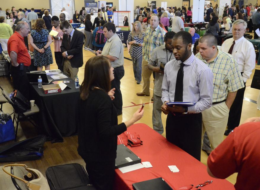Jennifer Wilhoit (center left) of U.S. Express talks with Devin Washington while others wait in line as 63 companies participate in a job fair at the Brainerd Crossroads in Chattanooga, Tenn., on Thursday, May 9, 2013. (AP Photo/Chattanooga Times Free Press, John Rawlston)