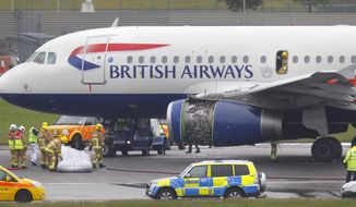 **FILE** Emergency services attend a British Airways passenger plane after it had to make an emergency landing at Heathrow Airport on May 24, 2013. (Associated Press)