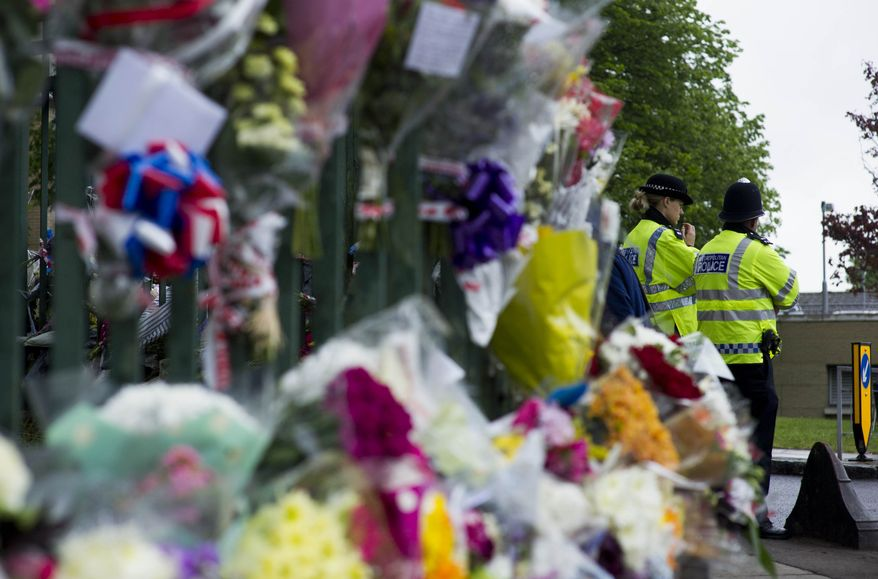 Police secure the area near flower tributes placed outside the Woolwich Barracks, in London, Friday, May 24, 2013, in response to the bloody attack on Wednesday when a British soldier was killed in the nearby street. (AP Photo/Bogdan Maran)