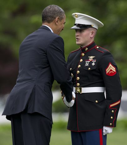 President Obama shakes hands with the Marine at the base of the steps of Marine One on the South Lawn of the White House on May 24, 2013. Obama forgot to salute the Marine as he boarded so he came back out to shake hands with the Marine. The president is traveling to Annapolis to deliver the commencement address at the United States Naval Academy. (Associated Press)