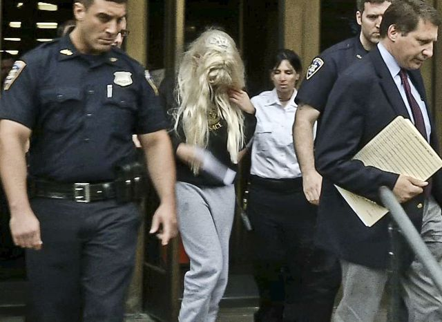 ** FILE ** Amanda Bynes (center), wearing sweats and a blonde wig, is escorted after a Manhattan criminal court appearance on May 24, 2013. (Associated Press/APTN)