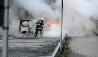 Firemen extinguish a burning car in the Stockholm suburb of Rinkeby after youths rioted in several different suburbs around Stockholm for a fourth consecutive night, late May 23, 2013. (AP Photo/Scanpix, Fredrik Sandberg)