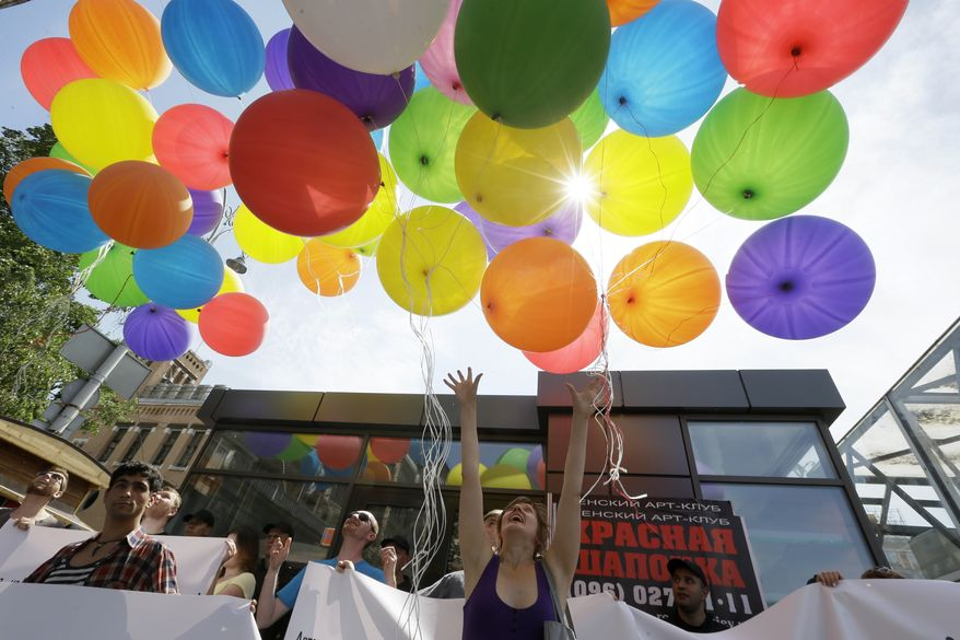 **FILE** Activists of a gay flash mob throw balloons into the air marking International Day Against Homophobia in Kiev on May 18, 2013. (Associated Press)
