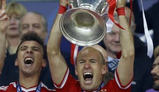 Bayern Munich's Arjen Robben of the Netherlands holds up the trophy after winning the Champions League Final soccer match against Borussia Dortmund at Wembley Stadium in London, Saturday May 25, 2013. (AP Photo/Kirsty Wigglesworth)