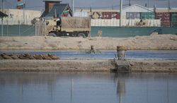 """The iconic """"Poo Pond,"""" a waste retention pond at the Kandahar Air Field known for its odor, was slated to close mid-2013. However, the pond, shown here in this May 17, 2013, photo, will remain open until the airfield's residents no longer need a place to discard waste, including that from portable toilets. (Kristina Wong/The Washington Times)"""