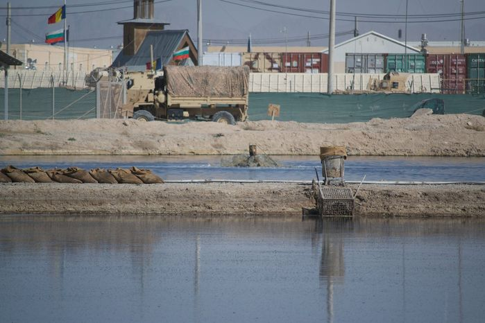 "The iconic ""Poo Pond,"" a waste retention pond at the Kandahar Air Field known for its odor, was slated to close mid-2013. However, the pond, shown here in this May 17, 2013, photo, will remain open until the ai"