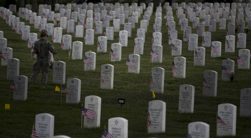 "A soldier with the 3rd U.S. Infantry Regiment, also known as ""The Old Guard,"" places flags at grave sites at Arlington National Cemetery in Arlington, Va., on Thursday, May 23, 2013, as part of the annual ""Flags-In"" ceremony in preparation for Memorial Day. (AP Photo/E"