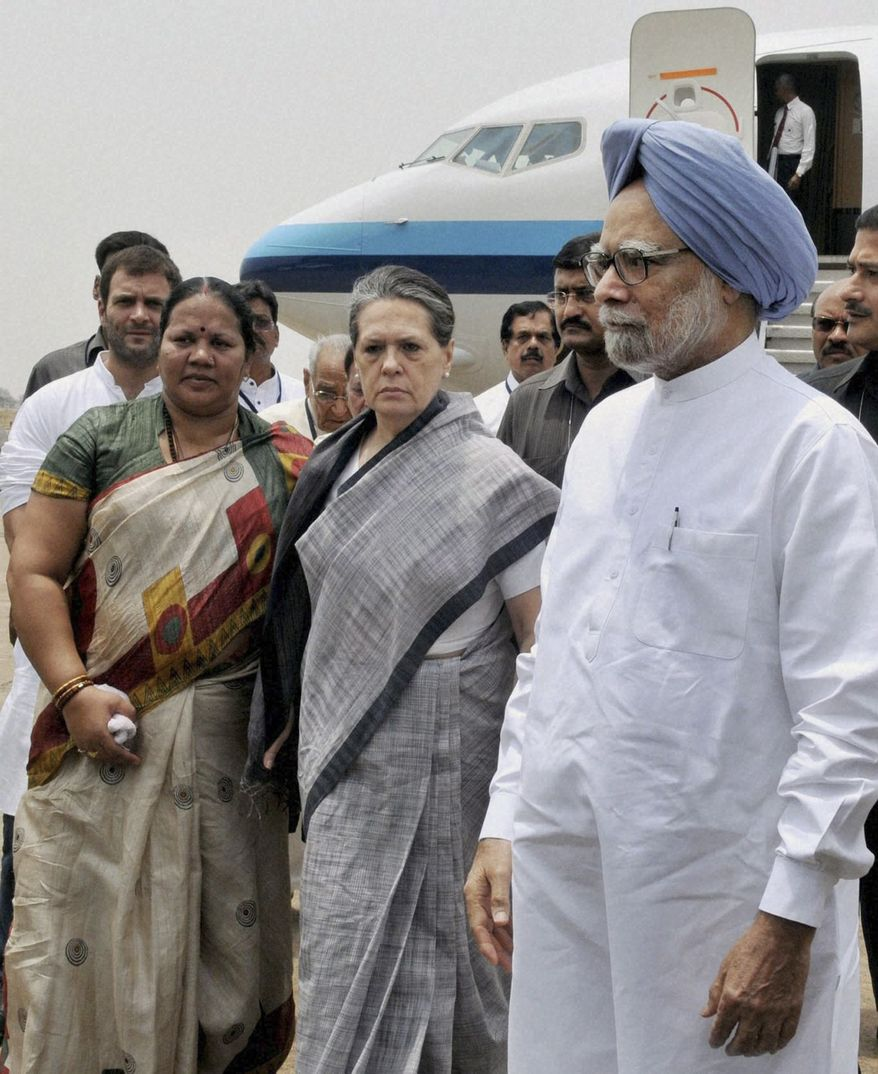 Indian Prime Minister Manmohan Singh (front right), Congress party President Sonia Gandhi (center) and party Vice President Rahul Gandhi (background left) arrive at the airport in Raipur, India, on Sunday, May 26, 2013, following Saturday's Maoist attack in a densely forested area in India's Chhattisgarh state. (AP Photo)