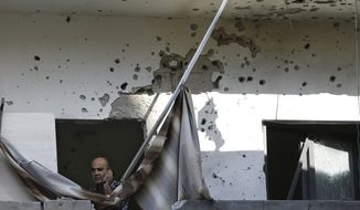 A Lebanese policeman speaks on his phone as he stands at a damaged balcony where a rocket struck an apartment in a building in the Chiyah district south of Beirut on Sunday, May 26, 2013. Rockets that slammed into two Hezbollah stronghold neighborhoods wounded at least four people. (AP Photo/Hussein Malla)