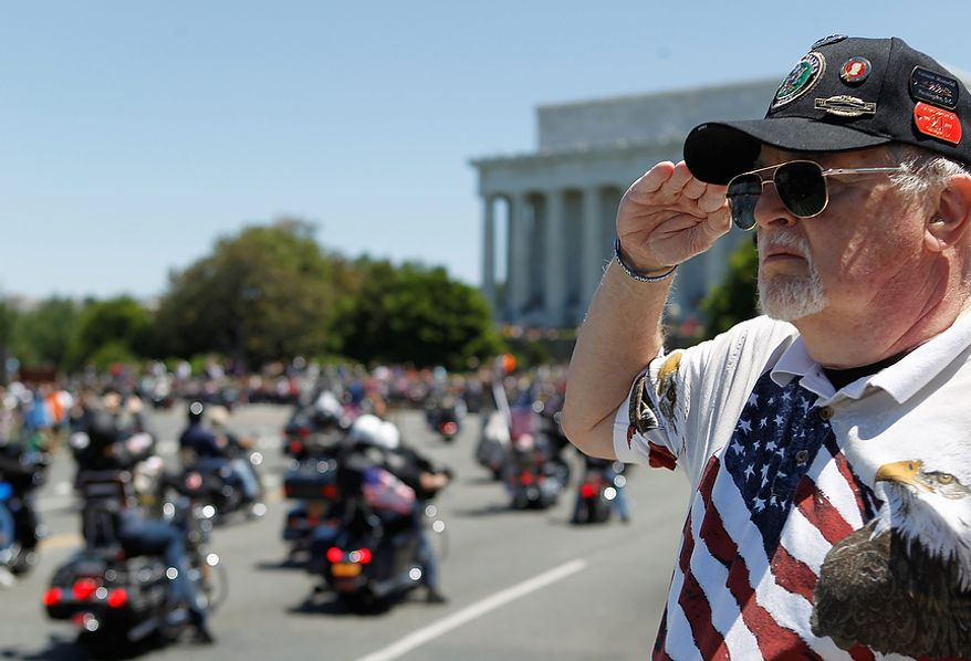 """Ken Caryl of Dale City, Va. salutes the motorcyclists, many of them are veterans, as they ride across the Memorial Bridge into Washington Sunday, May 26, 2013, during the annual Rolling Thunder """"Ride for Freedom"""" parade ahead of Monday's Memorial Day celebration. (AP Photo/Molly Riley)"""