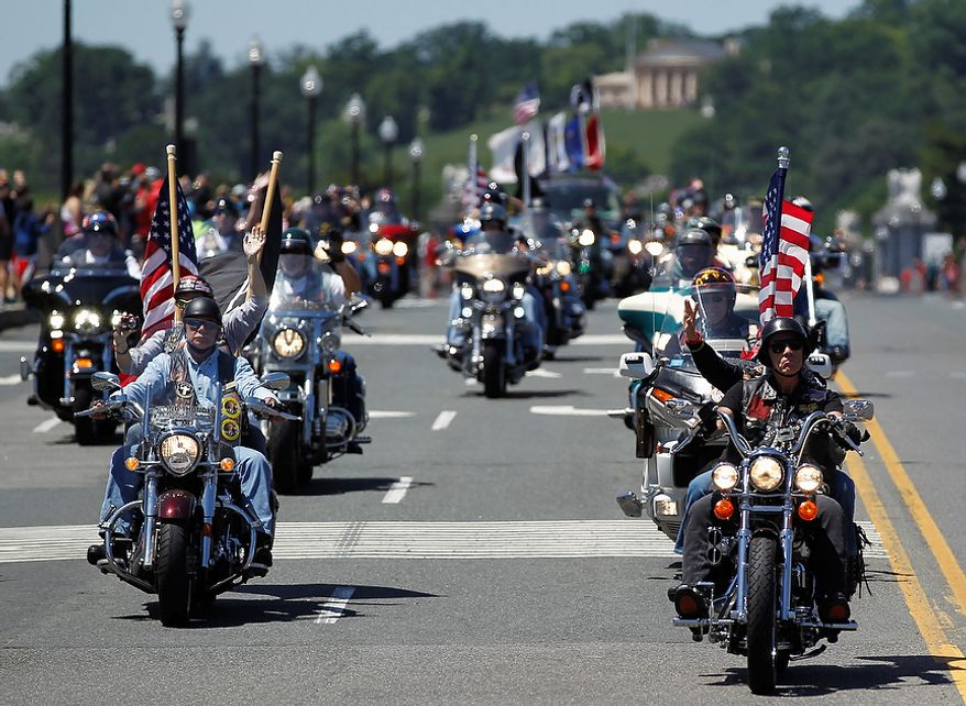 """Motorcyclists ride across the Memorial Bridge into Washington Sunday, May 26, 2013, during the annual Rolling Thunder """"Ride for Freedom"""" parade ahead of Monday's Memorial Day celebration. (AP Photo/Molly Riley)"""